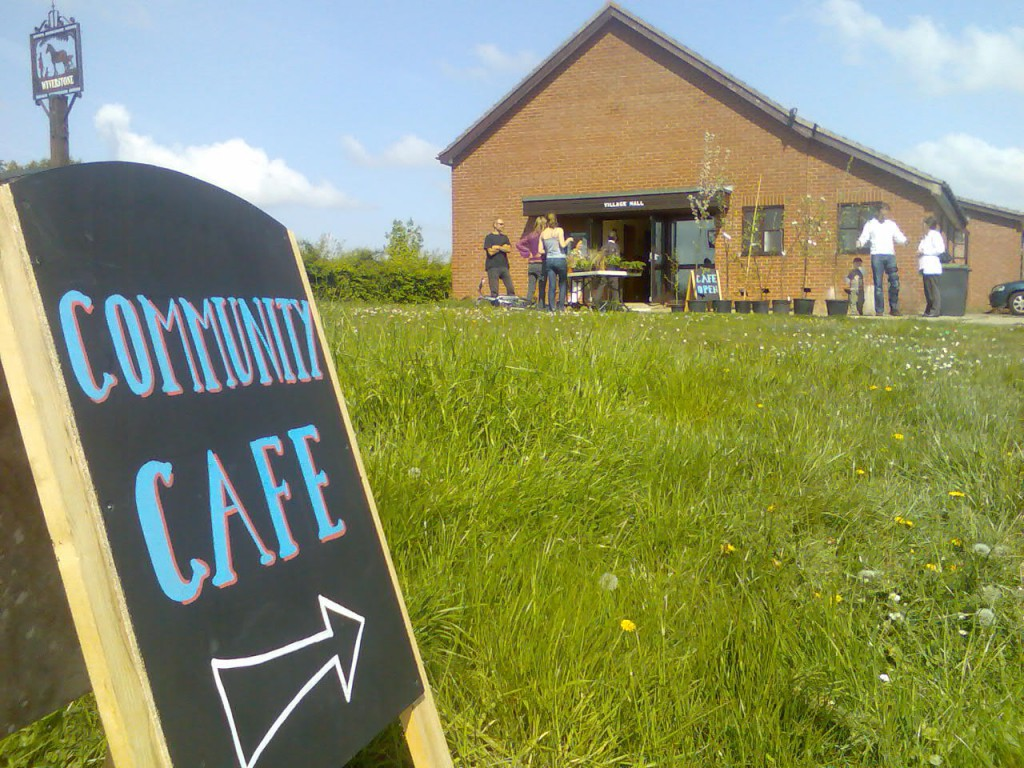 Photo of a chalked sign pointing to a community cafe